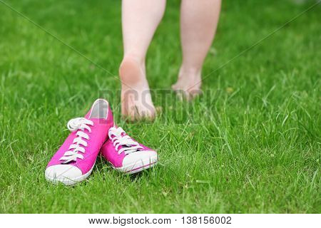 Female sneakers laying on green grass with female barefoot legs on background