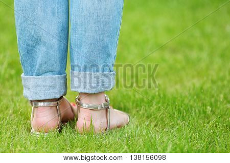 Female feet in sandals on green grass