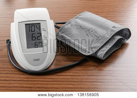 Digital blood pressure monitor on wooden background
