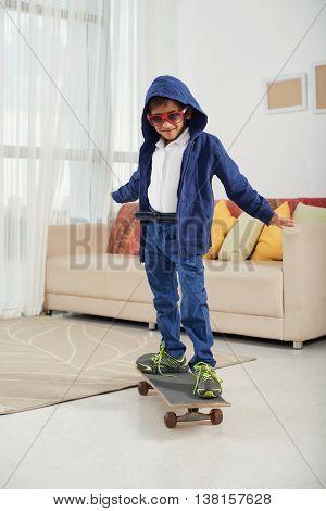 Preteen boy on skateboard in living room