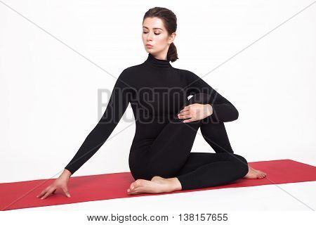 Beautiful athletic girl in a black suit doing yoga. ardha matsyendrasana asana - King Fish pose. Isolated on white background.