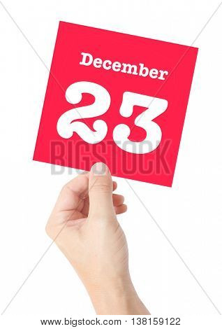 December 23 written on a card held by a hand