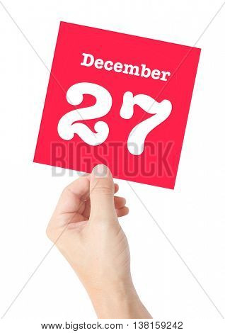 December 27 written on a card held by a hand