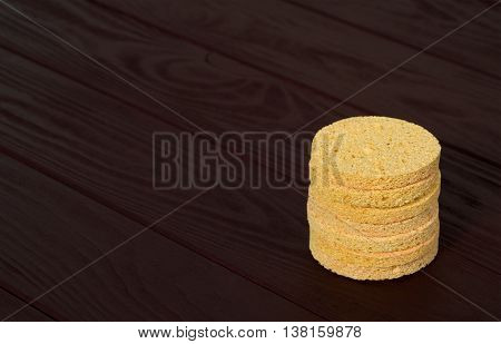 Still life stacked cosmetology yellow sponges on dark wood background closeup