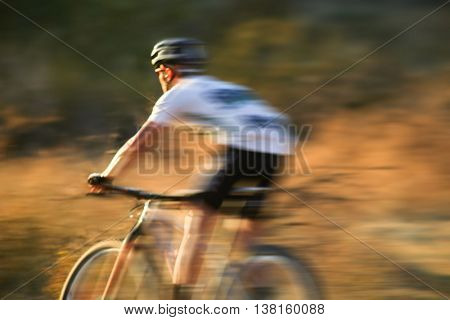 motion blur of a man riding a bicycle down a dirt trail in the back country to get away from the city toned with a retro vintage instagram filter app or action effect
