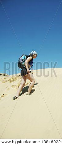 Girl going along dune in sand desert