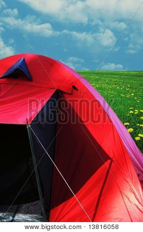Red tent on sunny grassland
