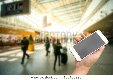 Hand Holding Smart Phone With Passengers Inside Transit Station Of Subway