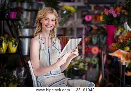 Portrait of smiling female florist using digital tablet in florist shop