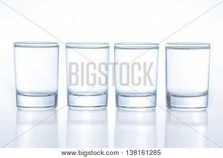 Few small shot glasses filled with alcohol on a light background