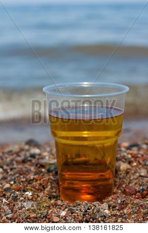 Glass of beer on the sea sand stones sunny warm day.