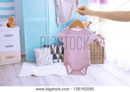 Female hand holding baby bodysuit in interior of child's room