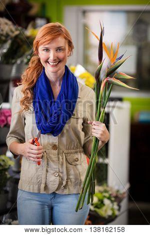 Portrait of smiling female florist trimming flower stem at flower shop