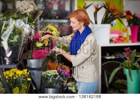 Happy female florist arranging flower bouquet in flower shop