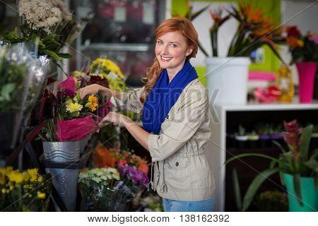 Portrait of happy female florist arranging flower bouquet in flower shop