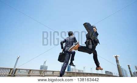 Business two men jumping on the road