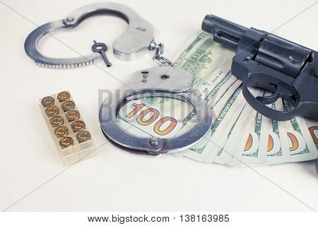 Pistol handcuffs ammo and money on a white background.
