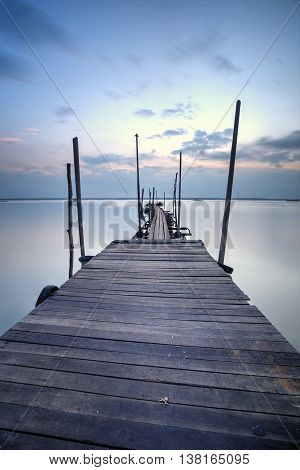 A wooden jetty at lake with blue hour sunset scenery in the background, Soft Focus due to Long Exposure Shot