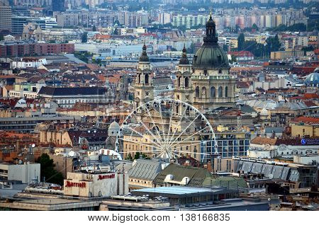 Beautiful Panorama Aerial view of St. Stephen's Basilica Big dome above buildings, Ferris wheel and rooftops under in Summer evening (Budapest, Hungary)