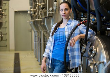 Portrait of beautiful brewer standing at bewery