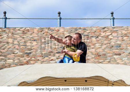 Father and son sitting on his haunches above the tunnel and point the finger at the sky and look at it