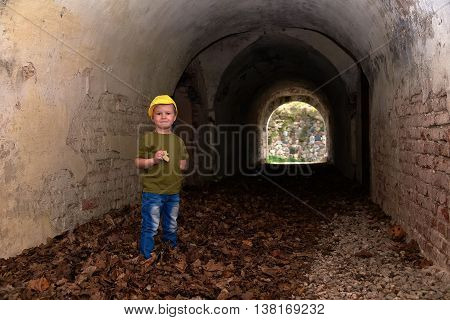 The boy in a yellow cap in the ruins