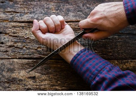 man holding a knife attempted suicide on wooden background