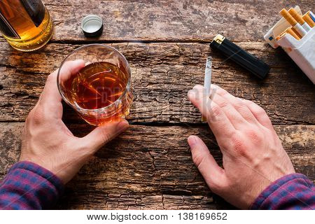man holding a glass of whiskey and smoking a cigarette