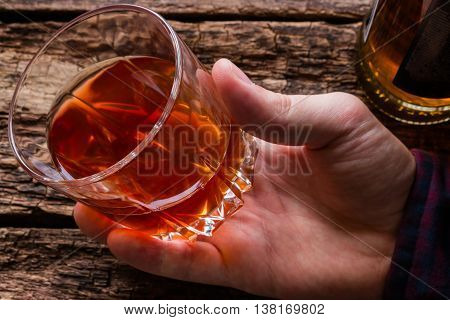 alcoholic man holding a glass of whiskey close-up