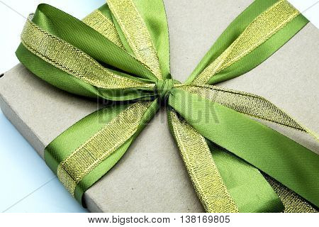 Close up of brown paper parcel/gift or present wrapping box with green and golden ribbons.