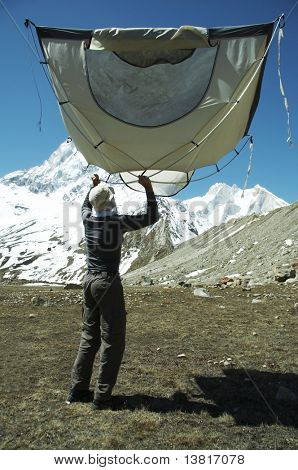 Climber and tent in Himalayan mountain