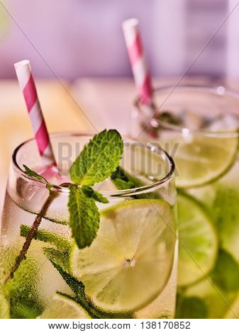 Alcohol drink. Part of two glasses with alcohol cocktail drink and ice cubes. Drink number hundred twelve cocktail mohito with straw. Country life. Light background.Close up.