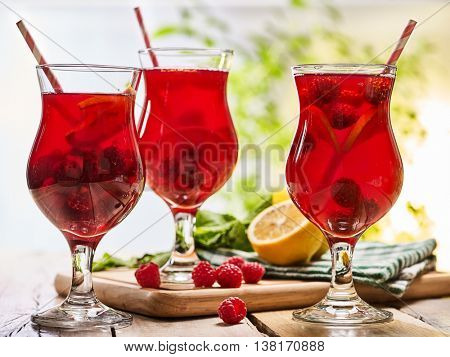 On wooden boards are ice cold beverage glasses with red raspberry lemon cocktail . Alcohol country cocktail beverage number hundred thirty two with drinking straw. Cocktail on outdoor.