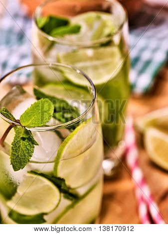 Alcohol drink. On wooden boards part of two glasses with lime alcohol drink and ice cubes. A drink number hundred eleven with two straw cocktails mohito and mint leaf. Country life. Light background.