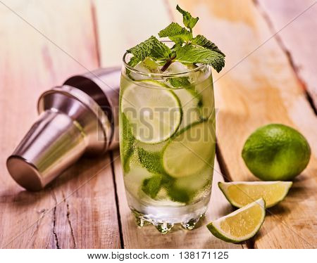 Alcohol drink. On wooden boards glass with alcohol drink and ice cubes. A drink number hundred eight cocktail mohito with cocktail shaker and mint leaf. Country life. Light background.