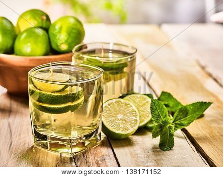Country drink. On wooden boards are two glasses with green transparent drink and lime glue bowl. Drink number hundred four mojito with mint leaf on sunlight . Country life. Light background.