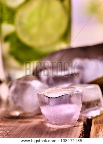 Chunks of ice cubes alcohol drink background on wooden boards. A drink number hundred nine cocktail mohito with slice lime and mint leaf.
