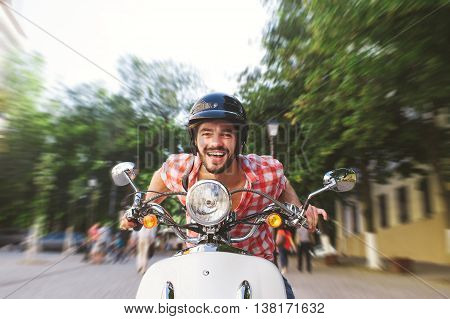 Smiling Young Man Riding Motor Scooter in the city. Speed motion blur concept.