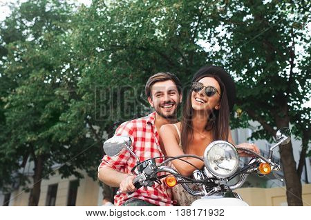 carefree couple having fun riding a scooter together. Young friends couple posing on a retro scooter outdoors with copy space