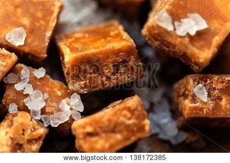 Sweet treats - Salted caramel pieces and sea salt close up. Butter caramel candy macro. Vintage rustic style