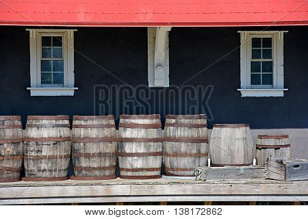 row of wooden barrels and crate on train station platform