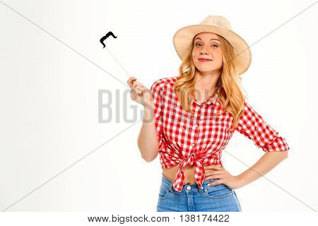 Portrait of young beautiful country girl in hat wearing fake mustache, smiling, looking at camera over white background. Copy space.