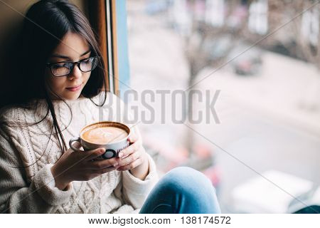 Teenage girl sitting at a window and holding a cup of coffee on a cold autumn day