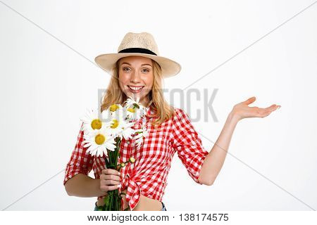 Portrait of young beautiful country girl in hat with chamomiles smiling, looking at camera, pointing hand in side over white background. Copy space.