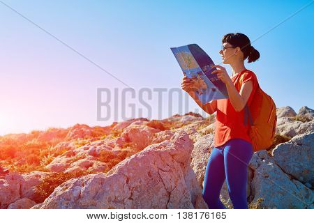 female hiker with backpack and map standing on the trail against sea and blue sky at early morning