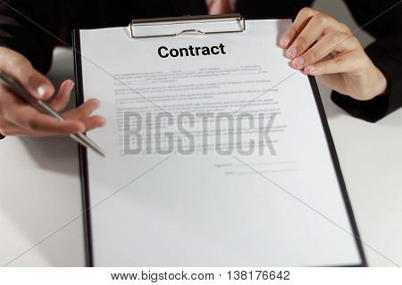 Businesswoman in suit holding and pointing the contract at her desk.