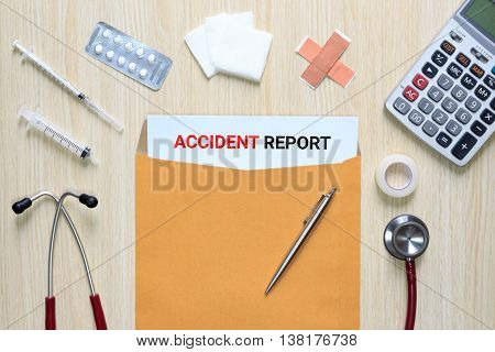 Top view of Accident report with letter envelope stethoscope hypodermic syringe plaster gauze medicine tape and calculator.