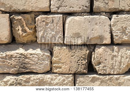 Weathered globerigina limestone wall large stone slabs as can be seen all over Malta. Shot straight-on in Valletta Malta Europe. Used in the 2015 filming of the Assassin's Creed movie.