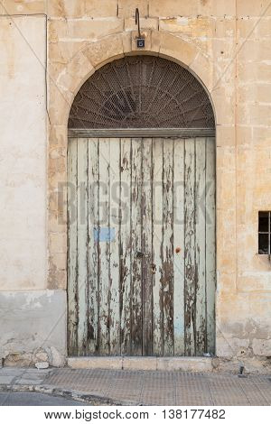 Ancient light green wooden doorway with flaking paint shot straight-on in Valletta Malta Europe. Used in the 2015 filming of the Assassin's Creed movie.