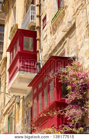 Red wooden balconies against warm sunlit limestone walls with a colorful vine plant growing Valletta Malta June 2016